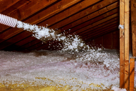 Worker Spraying mineral rock wool of house attic insulation