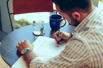 Businessman writing in book while sitting in office