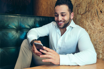 Smiling man sitting in cafe, looking at smartphone