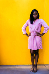 Young woman posing against yellow wall