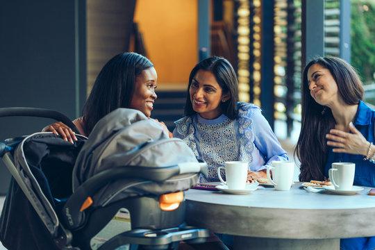 Smiling female friends talking in coffee shop