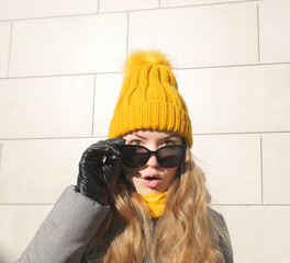 Portrait of a beautiful girl in a yellow hat and black sunglasses. Autumn concept. Portrait closeup beautiful young girl in yellow hat over bright background.