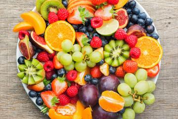 Wall Mural - Healthy fruit platter, strawberries raspberries oranges plums apples kiwis grapes blueberries on the dark grey wooden table, top view, close up, selective focus