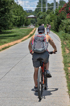 The Atlanta BeltLine (path/greenspace) with unidentifiable people biking and walking on a warm summer afternoon