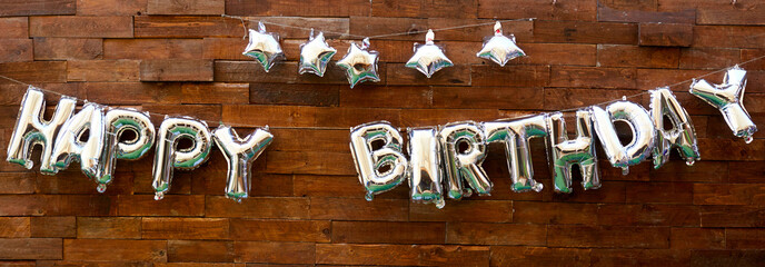 inscription with balloons happy birthday on a wooden background