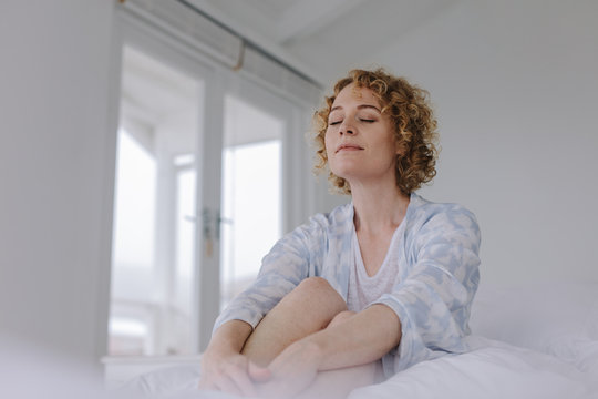Woman sitting on bed after waking up