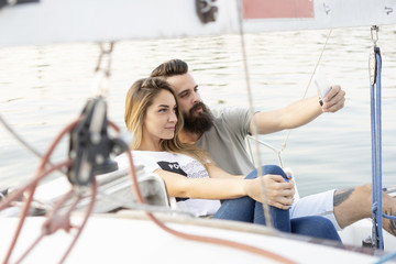 Attractive couple relaxes, taking photos and using a smartphone on a sailboat