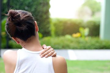 Women have neck pain, shoulder pain, at the park health concept.