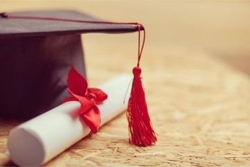 Graduation hat with tassel, diploma with red