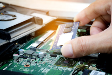 Hand of computer engineering brings computer memory components into ram slots for maintenance.Technology concept