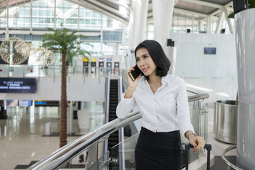 Asian businesswoman with phone at airport
