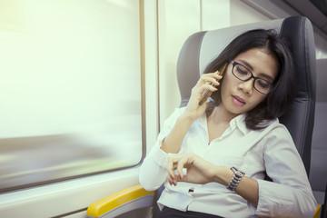Female entrepreneur talking on phone in train