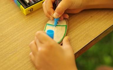 木の板に絵を描く子供
