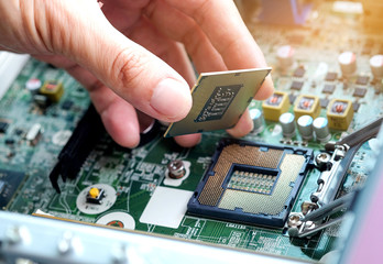 Hand of computer engineering brings computer cpu processor memory change components into socket processor for maintenance.Technology and development concept