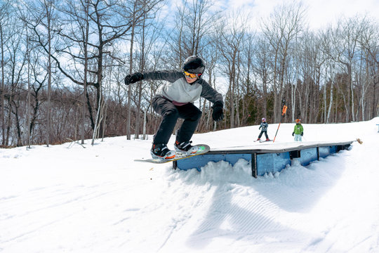 Boy performs trick on snowboard