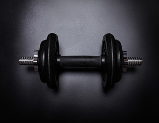 Dumbbell on black background. Power training concept.