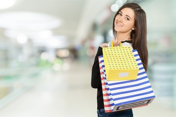 Young woman with shopping bags on blurred shopping mall