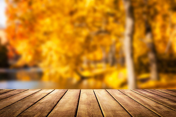 Wooden table top on blur autumn background