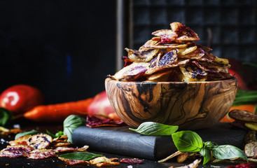 Chips from purple and red potatoes in wooden bowl on background of vegetables, selective focus