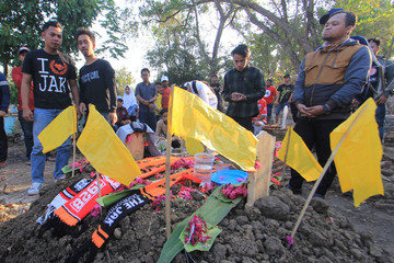 Persija supporters stand around the grave of Haringga Sirila, a Persija Jakarta fan who was killed by a mob of supporters of a rival club, in Indramayu