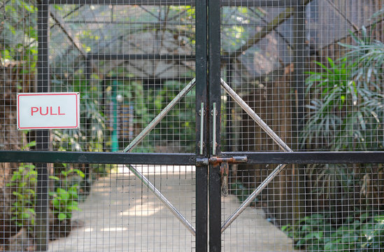 """Iron cage door in zoo with """"PULL"""" label."""