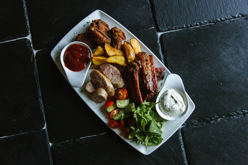 Meat plate with pork ribs, chicken, fried potatoes, cheese balls, croutons, sausages with sauce on black background