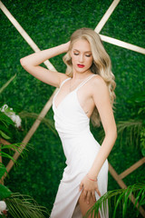 Beautiful young girl with blond hair and a Hollywood wave and with red lipstick on her lips in a white evening dress in the floor on a green photo zone with tropical leaves, white orchids and roses