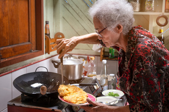 Senior asian woman cooking omelet in kitchen at home,lifestyle of asian old woman concept