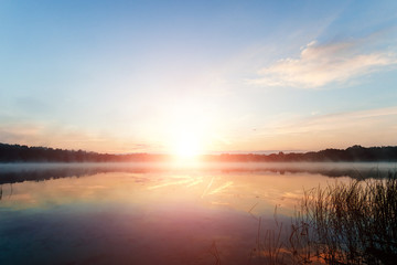 Beautiful, pink violet dawn over the lake. Fog over the lake, the rays of the sun, very dense fog, dawn, the blue sky over the lake, the morning comes, the forest reflects in the water.