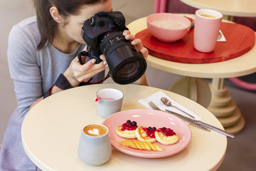 Young woman food photographer blogger shoots Breakfast in cafe,