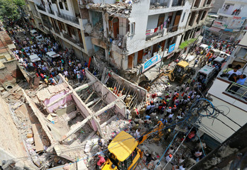Rescuers search for survivors amidst the rubble after a building collapsed in New Delhi