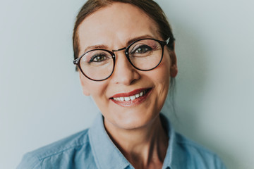 Beautiful mature woman smiling.Close up portrait of beautiful older woman smiling and standing by wall.Portrait of business woman with glasses smiling.