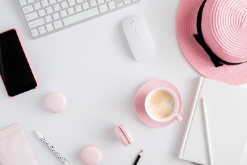 Trendy feminine home office workspace. White office desk. Laptop, coffee cup and macaroons, phone, hat, notebook, pencil. Flat lay, top view, copy space