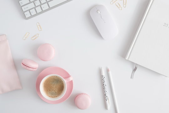 Trendy feminine home office workspace. White office desk. Laptop, coffee cup and macaroons, phone, notebook, pencil. Flat lay, top view, copy space