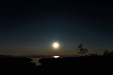 Night moon sky, full moon, Moon over the lake. Night landscape. Reflection of the rays from the moon in the water.