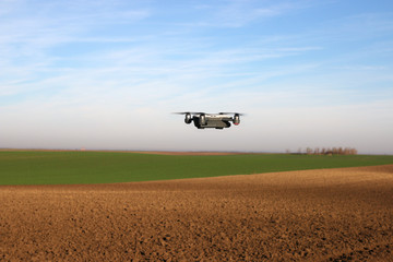 The drone is flying over the plowed field agriculture
