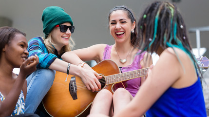 Young woman assisting her friend to play an music on guitar