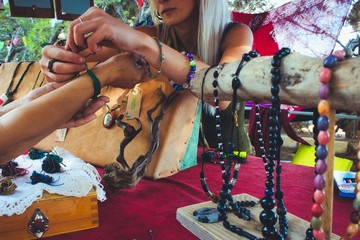 A woman selling homemade craft jewelry from a market stall at a hippy festival