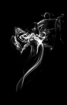 white smoke or dust, wavy and swirly on black background.  perfect for compositing eg. hot tea, cigarettes or other smoking things.