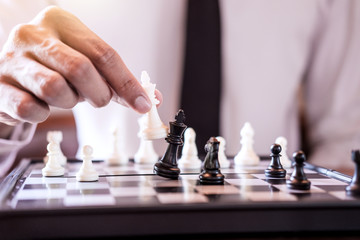 Hand of confident businessman use king chess piece white playing chess game to crash overthrow the opposite team and development analysis new strategy plan, business strategy for win and success