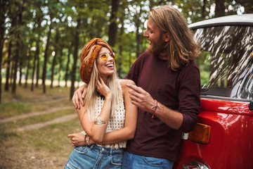 Young hippy couple man and woman smiling, and hugging each other while standing near minivan in forest