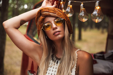 Photo of beautiful hippie woman, wearing stylish accessories looking forward while resting in forest camp