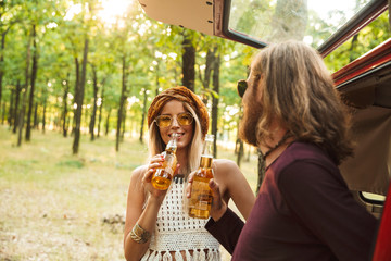 Photo of beautiful hippie couple man and woman smiling, and drinking beer in forest near retro minivan