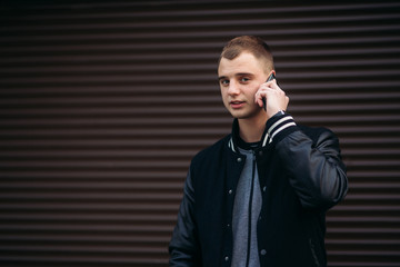 A young guy in a black jacket against a background of dark striped walls uses the phone