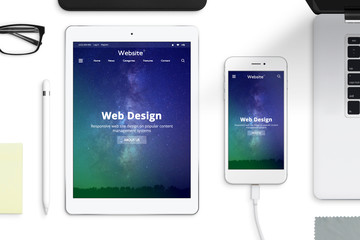Responsive web site desing on tablet and smart phone screen. Office desk composition. Top view.