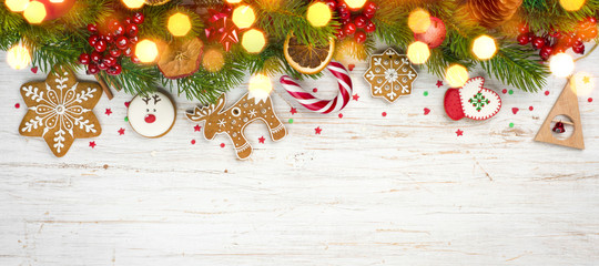 Glittered сhristmas background, decorated holiday tree branches and gingerbread cookies