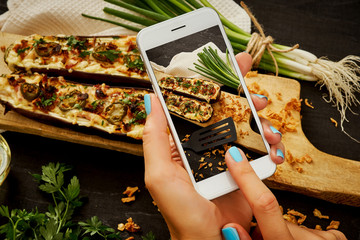woman's hands are holding the phone and taking a picture of a delicious courgette casserole on a woody table
