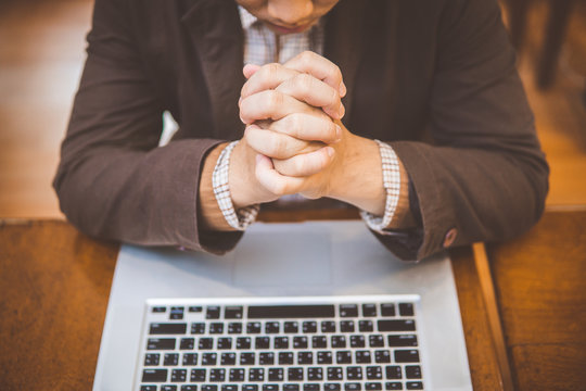 Smiling businessman with closed eyes praying in front of laptop.