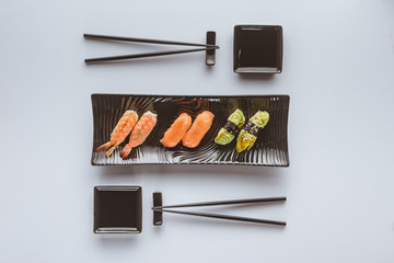 top view of tasty sushi set and chopsticks isolated on white