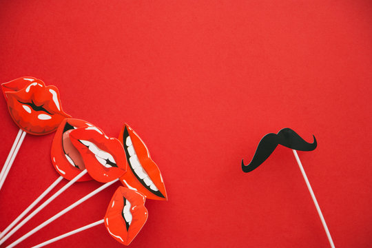 flatlay overhead top black paper photo booth props emotions lip and mustache red background copy space